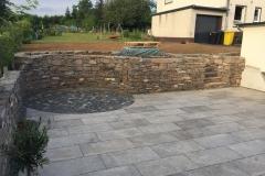 Natursteinmauer mit Terrasse links